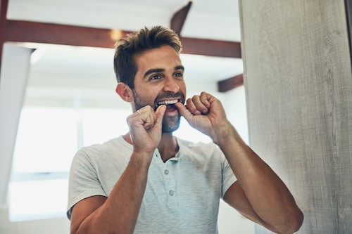 adult man flossing in front of a mirror copy